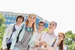 Estudiantes jovenes sonrientes que se unen en el campus de la universidad Imagen de archivo
