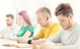 Estudiantes jovenes y elegantes que aprenden en una sala de clase Imagenes de archivo