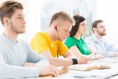 Estudiantes jovenes y elegantes que estudian en una sala de clase Imágenes de archivo libres de regalías