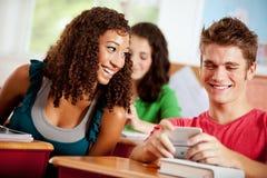 Estudiantes: La muchacha mira encima el teléfono celular del individuo Imagen de archivo