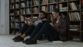 Estudiantes listos de los ratones de biblioteca en estudiar de la biblioteca almacen de video