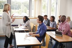 Estudiantes maduros de Teaching Class Of del profesor particular de sexo femenino foto de archivo libre de regalías