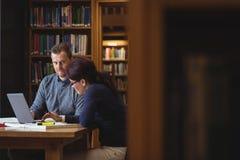 Estudiantes maduros que trabajan junto en biblioteca de universidad Imagen de archivo