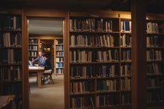 Estudiantes maduros que trabajan junto en biblioteca de universidad Fotos de archivo