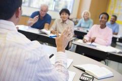 Estudiantes maduros y su profesor en una sala de clase Foto de archivo libre de regalías