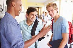 Estudiantes masculinos de la High School secundaria por los armarios que miran el teléfono móvil imagenes de archivo