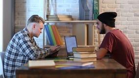 Estudiantes masculinos serios en biblioteca que estudian para el examen metrajes