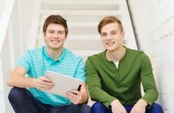 Estudiantes masculinos sonrientes con el ordenador de la PC de la tableta Fotografía de archivo
