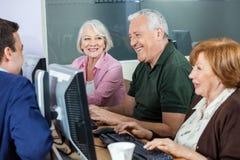 Estudiantes mayores felices que discuten con el profesor In Computer Class Fotos de archivo