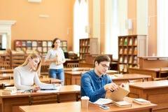 Estudiantes modernos que visitan la biblioteca imagen de archivo
