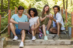 Estudiantes multiétnicos de los amigos al aire libre usando el teléfono móvil y el ordenador portátil fotos de archivo