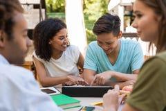 Estudiantes multiétnicos jovenes alegres de los amigos al aire libre usando la tableta imagen de archivo libre de regalías