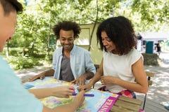 Estudiantes multiétnicos jovenes concentrados de los amigos al aire libre que estudian Fotografía de archivo libre de regalías