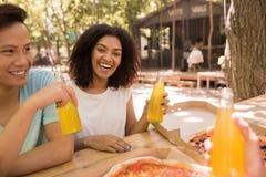 Estudiantes multiétnicos jovenes felices de los amigos al aire libre que beben el jugo que come la pizza Fotos de archivo