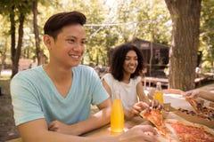 Estudiantes multiétnicos jovenes sonrientes de los amigos al aire libre que beben el jugo que come la pizza Imagen de archivo libre de regalías