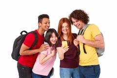 Estudiantes multiétnicos que hojean smartphone junto foto de archivo libre de regalías