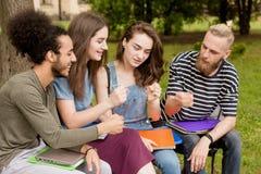Estudiantes multiétnicos que se sientan en el banco que juega a juegos Imagen de archivo libre de regalías