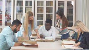 Estudiantes multirraciales diversos que pasan el tiempo libre en biblioteca con el libro viejo grande metrajes