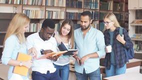 Estudiantes multirraciales que se divierten en biblioteca mientras que se prepara para los exámenes almacen de metraje de vídeo