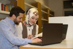 Estudiantes musulmanes en biblioteca Foto de archivo libre de regalías
