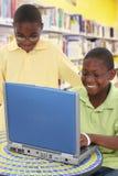 Estudiantes negros que comparten la computadora portátil en la escuela Fotos de archivo