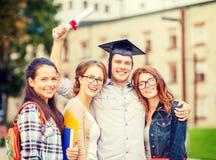Estudiantes o adolescentes con los ficheros y el diploma Imagen de archivo