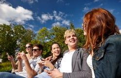 Estudiantes o adolescentes con smartphones en el campus Imágenes de archivo libres de regalías