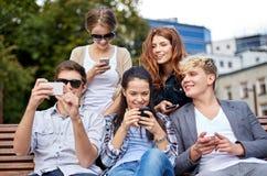 Estudiantes o adolescentes con smartphones en el campus Imagen de archivo