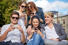 Estudiantes o adolescentes con smartphones en el campus Imagen de archivo libre de regalías