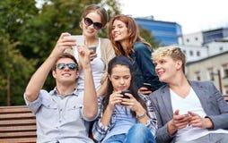 Estudiantes o adolescentes con smartphones en el campus Fotos de archivo libres de regalías