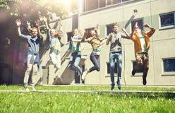 Estudiantes o amigos adolescentes felices que saltan al aire libre Imagenes de archivo