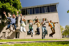 Estudiantes o amigos adolescentes felices que saltan al aire libre Fotos de archivo libres de regalías