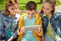 Estudiantes o amigos con PC de la tableta al aire libre Imagen de archivo libre de regalías