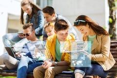 Estudiantes o amigos felices con PC de la tableta al aire libre Foto de archivo libre de regalías