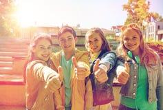 Estudiantes o amigos felices que muestran los pulgares para arriba Imagen de archivo