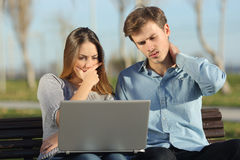 Estudiantes o empresarios preocupantes que miran un ordenador portátil al aire libre Imágenes de archivo libres de regalías