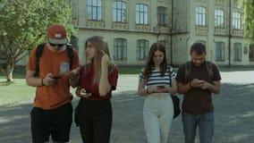 Estudiantes ocupados con los teléfonos móviles que caminan en campus metrajes