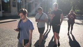 Estudiantes ocupados con smartphones en campus universitario almacen de metraje de vídeo
