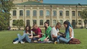 Estudiantes ocupados que ignoran m?s viejo un estudiar al aire libre metrajes