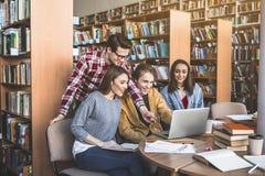 Estudiantes positivos que trabajan con el ordenador portátil Imagenes de archivo