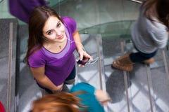 Estudiantes que acometen arriba y abajo de una escalera ocupada Fotos de archivo libres de regalías