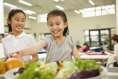Estudiantes que alcanzan para la comida sana en cafetería de la escuela Imagen de archivo libre de regalías