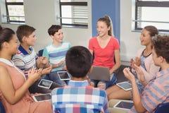 Estudiantes que aprecian al compañero de clase después de la presentación en sala de clase Imagen de archivo libre de regalías
