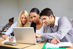 Estudiantes que aprenden en la computadora portátil Imágenes de archivo libres de regalías