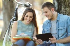 Estudiantes que aprenden junto en línea y que toman notas Imagen de archivo libre de regalías
