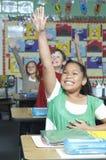 Estudiantes que aumentan las manos a la respuesta fotografía de archivo libre de regalías