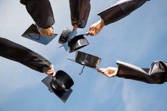 Estudiantes que aumentan tableros del mortero contra el cielo encendido Imagenes de archivo