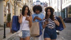 Estudiantes que caminan con los panieres y los teléfonos almacen de video