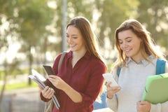 Estudiantes que caminan con los teléfonos elegantes Imagen de archivo libre de regalías