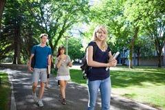 Estudiantes que caminan en campus Imágenes de archivo libres de regalías